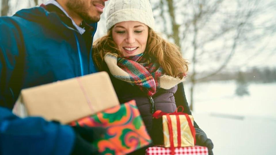 Smiling diverse couple holding Christmas presents while walking through a winter forest