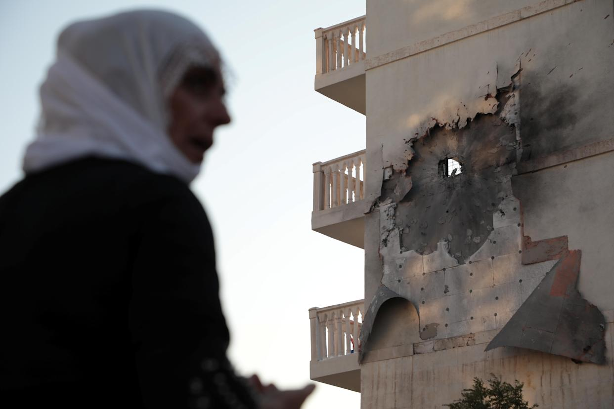 A woman stands in front of an apartment building which was damaged by a rocket fired from Syria, in Nusaybin, Turkey, Oct. 10, 2019. (Photo: Sertac Kayar/Reuters)