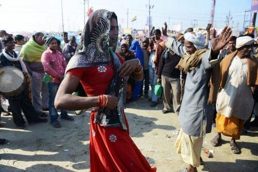 <p>An elderly Indian man dances with another man dressed as a woman after taking a dip in the River Ganges during the Kumbh Mela in Allahabad on February 9, 2013. Tens of millions of Hindu pilgrims are preparing to cleanse their sins with a plunge into the sacred River Ganges, ahead of the most auspicious day of the world's largest religious festival.</p>
