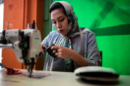 Afghan refugee and designer-maker Fariba Amini, 31, works on a sewing machine in a studio in Athens