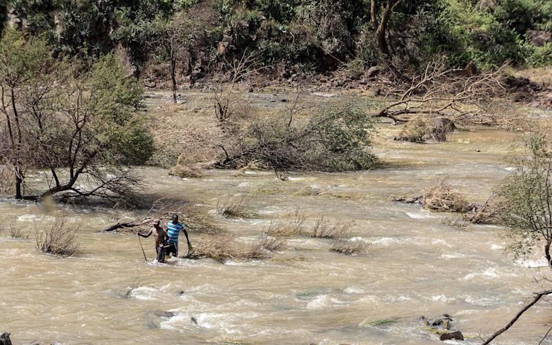 Two gold panners men carry a radio and a metal detector machine as they walk across the overflowing Ncema - AFP or licensors