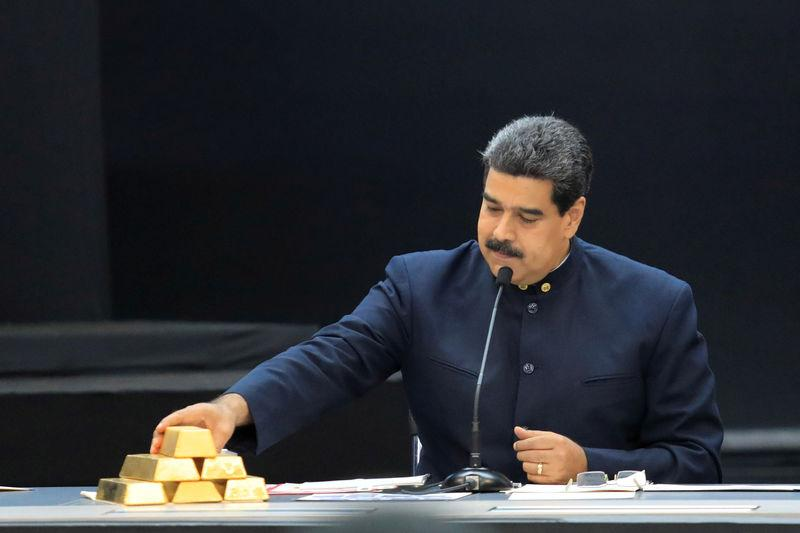 FILE PHOTO: Venezuela's President Nicolas Maduro touches a gold bar as he speaks during a meeting with the ministers responsible for the economic sector at Miraflores Palace in Caraca