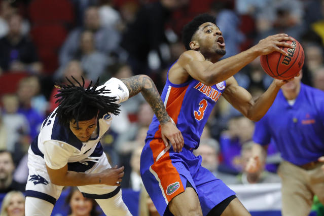 Florida guard Jalen Hudson (3) grabs a loose ball over Nevada guard Jazz Johnson, left, during a first round men's college basketball game in the NCAA Tournament, Thursday, March 21, 2019, in Des Moines, Iowa. (AP Photo/Charlie Neibergall)