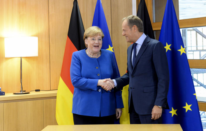 German Chancellor Angela Merkel, left, shakes hands with European Council President Donald Tusk prior to a meeting at an EU summit in Brussels, Thursday, Oct. 17, 2019. Britain and the European Union reached a new tentative Brexit deal on Thursday, hoping to finally escape the acrimony, divisions and frustration of their three-year divorce battle. (Johanna Geron, Pool Photo via AP)