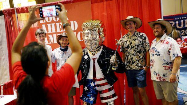PHOTO: People take a picture with former President Donald Trump's statue on display at the Conservative Political Action Conference held in the Hyatt Regency on Feb. 27, 2021 in Orlando, Fla.  (Joe Raedle/Getty Images)
