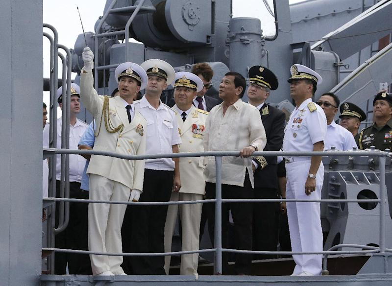 FILE - In this Jan. 6, 2017, file photo, Philippine President Rodrigo Duterte, center, watches as Russian navy officers show the weapons on board the Russian anti-submarine Navy vessel Admiral Tributs in Manila, Philippines. A flurry of goodwill visits by ships and submarines has marked the new year in the South China Sea. In the Philippines, two Russian warships docked in Manila for a five-day visit in a showcase by Moscow to demonstrate what it can offer to a traditional U.S. ally. (AP Photo/Aaron Favila, File)