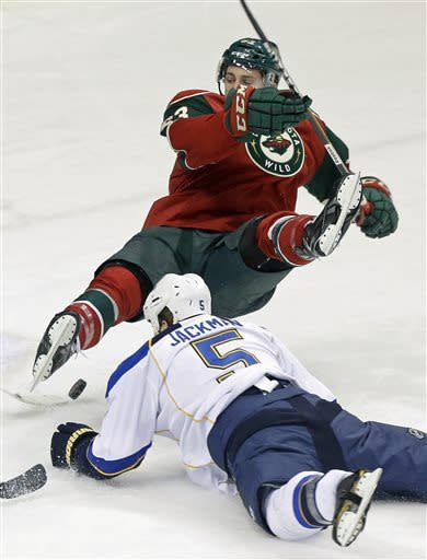 Minnesota Wild's Charlie Coyle, top, is upended by St. Louis Blues' Barret Jackman (5) as he shoots in the first period of an NHL hockey game on Thursday, April 11, 2013, in St. Paul. (AP Photo/Jim Mone)