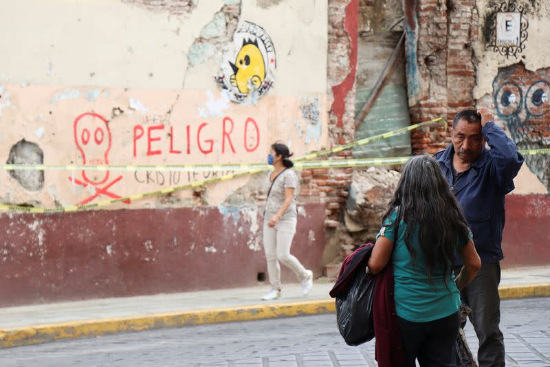 People talk near a building damaged during a quake, in Oaxaca