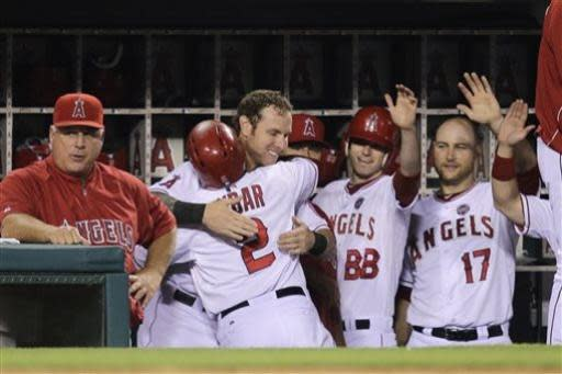 Los Angeles Angels' Erick Aybar (2) gets a hug from Josh Hamilton while celebrating a home run by Aybar during the fifth inning of a baseball game against the Oakland Athletics on Friday, July 19, 2013, in Anaheim, Calif. (AP Photo/Jae C. Hong)