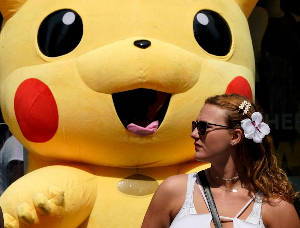 A person walks past a Pikachu mascot at Times Square on July 22, 2021, as the Delta Covid surge is renewing calls for mask mandates in New York. - New York City will require public hospital workers to get vaccinated or take a weekly coronavirus test, Mayor Bill de Blasio said on July 21, as the metropolis faces an uptick in cases fueled by the Delta variant. (Photo by TIMOTHY A. CLARY / AFP) (Photo by TIMOTHY A. CLARY/AFP via Getty Images)