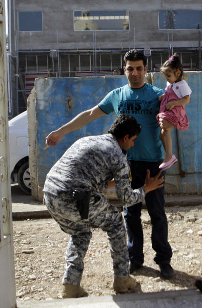 A policeman searches a man outside the Virgin Mary Chaldean Church before Easter mass at Virgin Mary Chaldean Church in Baghdad, Iraq, Sunday, March 31, 2013. The Chaldean Church is an Eastern Rite church affiliated with the Roman Catholic Church. (AP Photo/ Khalid Mohammed)