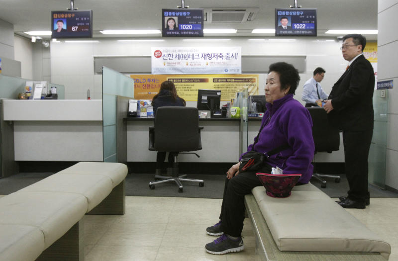 A customer sits in a branch of Shinhan Bank in Seoul, South Korea, while the bank's computer networks are paralyzed Wednesday, March 20, 2013. Police and South Korean officials were investigating the simultaneous shutdown Wednesday of computer networks at several major broadcasters and banks. While the cause wasn't immediately clear, speculation centered on a possible North Korean cyberattack. (AP Photo/Ahn Young-joon)