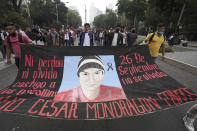 Supporters and relatives of 43 missing university students hold a banner with the likeness of one of the missing students, as they march on the seventh anniversary of their disappearance, in Mexico City, Sunday, Sept. 26, 2021. Relatives continue to demand justice for the Ayotzinapa students who were allegedly taken from the buses by the local police and handed over to a gang of drug traffickers. (AP Photo/Marco Ugarte)