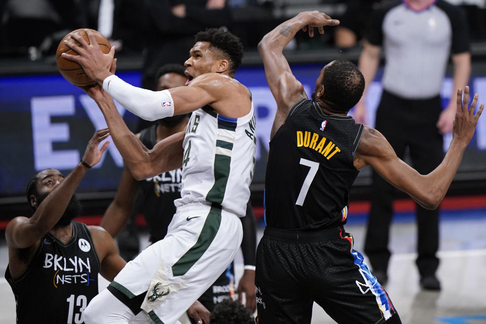 Brooklyn Nets guard James Harden (13) and Brooklyn Nets forward Kevin Durant (7) try to contain Milwaukee Bucks forward Giannis Antetokounmpo (34) in Game 5 of a second-round NBA basketball playoff series, Tuesday, June 15, 2021, in New York. (AP Photo/Kathy Willens)