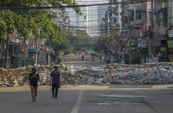 People walk along a deserted road blocked with improvised barricades build by anti-coup protesters to secure a neighborhood in Yangon, Myanmar, Thursday, March 18, 2021. (AP Photo)