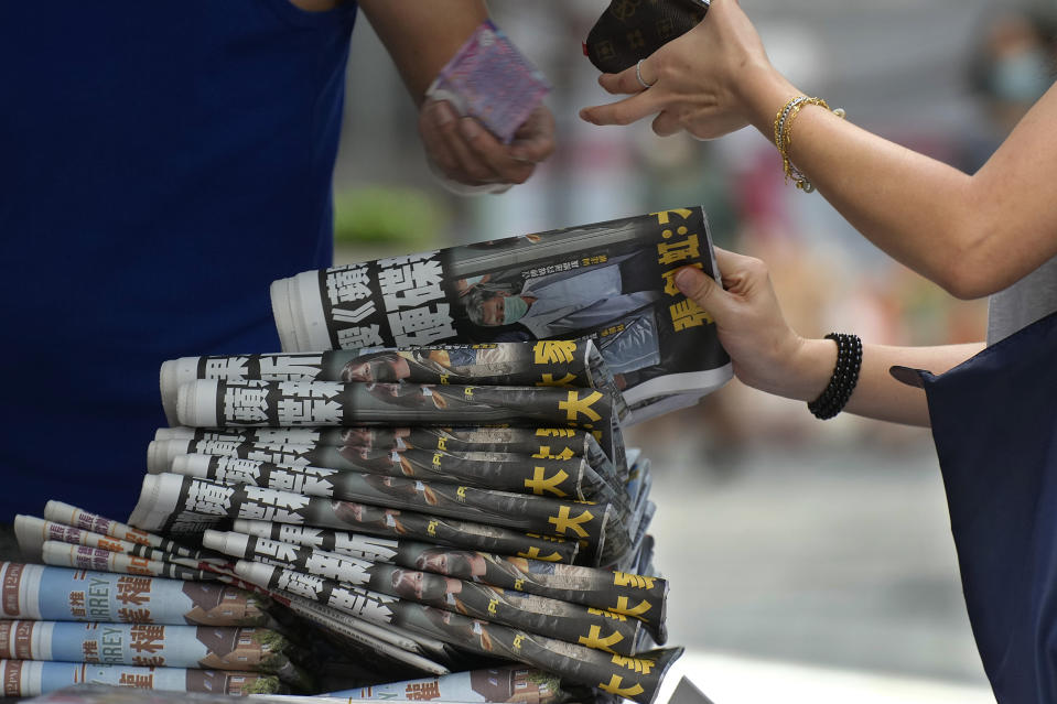 People buy Apple Daily at a news stand at a downtown street in Hong Kong Friday, June 18, 2021. The pro-democracy paper increased its print run to 500,000 copies on Friday, a day after police arrested five top editors and executives and froze $2.3 million in assets linked to the media company. (AP Photo/Vincent Yu)
