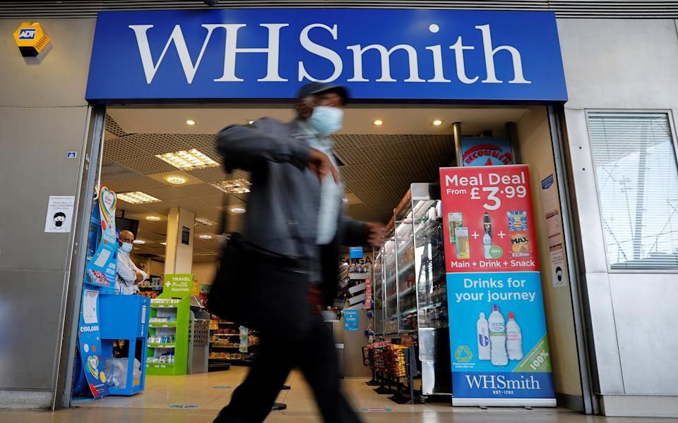 Pedestrians wearing a face mask or covering due to the COVID-19 pandemic, walk past a WH Smith store in London on August 5, 2020, following the announcement the retailer could cut 1500 jobs, and close up to 14 stores. - WH Smith said on Wednesday that it is planning to cut up to 1,500 jobs, due to the slow recovery from the COVID-19 lockdown. (Photo by Tolga Akmen / AFP) (Photo by TOLGA AKMEN/AFP via Getty Images)