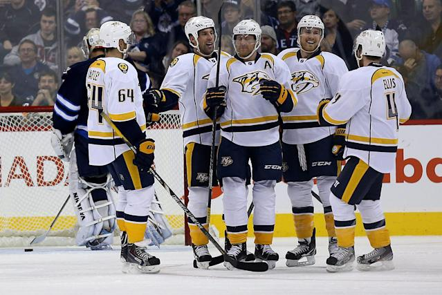From left, Nashville Predators' Victor Bartley (64), David Legwand, Patric Hornqvist, Colin Wilson and Ryan Ellis (4) celebrate after the puck went past Winnipeg Jets' goalie Ondrej Pavelec off of Zach Bogosian during the second period of an NHL hockey game in Winnipeg, Manitoba, Sunday, Oct. 20, 2013. Nashville Predators' Patric Hornqvist was given credit for the goal. (AP Photo/The Canadian Press, Trevor Hagan)