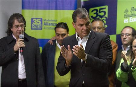 Ecuador's President Correa is introduced by the director of his political party Mora before addressing the media on the results based on exit polls in the local elections in Quito