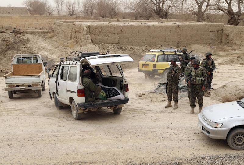 In this Sunday, March 11, 2012 photo, Afghan soldiers, right, stand near a vehicle carrying bodies of civilians allegedly killed in a shooting rampage by a U.S. soldier in Panjwai, Kandahar province south of Kabul, Afghanistan. The United States has paid $50,000 in compensation for each Afghan killed and $11,000 for each person wounded in the shooting spree allegedly committed by a U.S. soldier in southern Afghanistan, an Afghan official and a community elder said Sunday. The sums, much larger than typical payments made by the U.S. to families of civilians killed in military operations in Afghanistan, come as the U.S. tries to mend relations following the killing rampage that has threatened to undermine the international effort here. (AP Photo/Allauddin Khan)