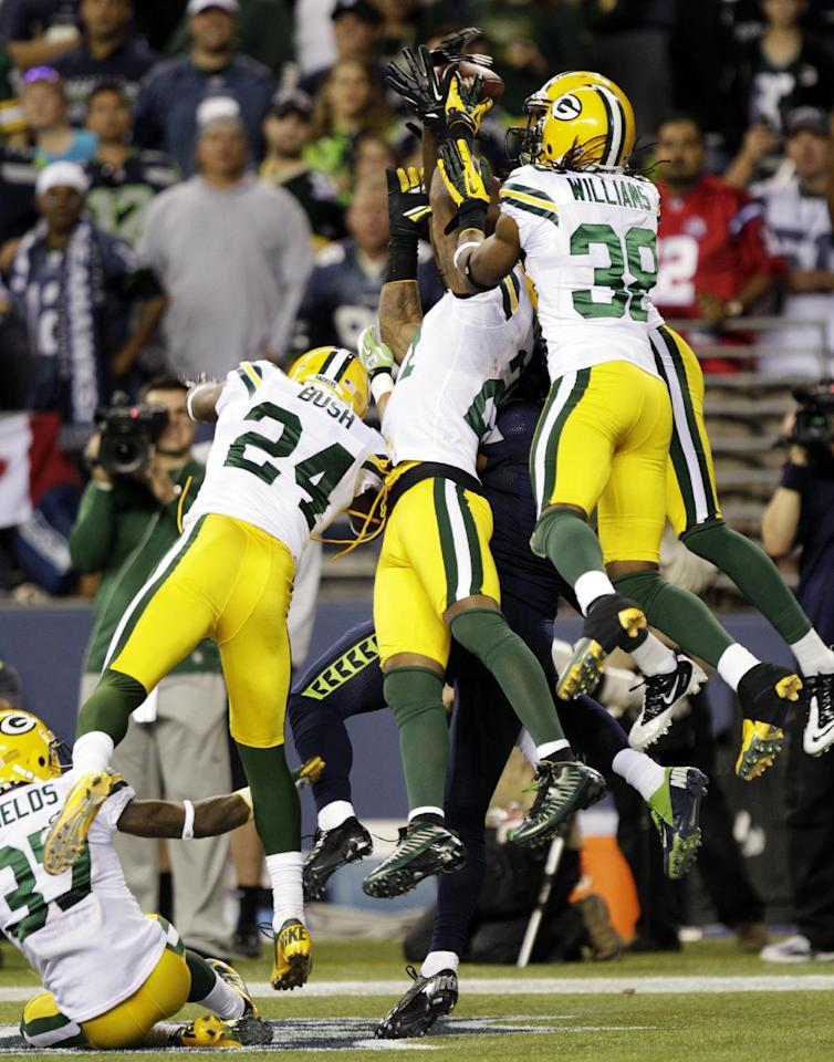 Seattle Seahawks wide receiver Golden Tate, obscured, comes down with the ball in the end zone for a touchdown as Green Bay Packers' Jarrett Bush (24) and Tramon Williams (38) defend in the second half of an NFL football game, Monday, Sept. 24, 2012, in Seattle. The Seahawks won 14-12. (AP Photo/Ted S. Warren)