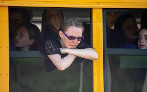 Evacuated middle school students wait on a bus outside Noblesville High School - Credit: Getty
