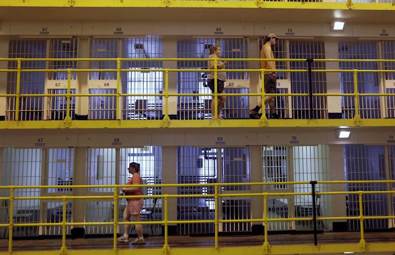 People walk by cells at the Cell Block 7 Prison Museum at the State Prison of Southern Michigan in Jackson, Mich., Saturday, June 28, 2014.