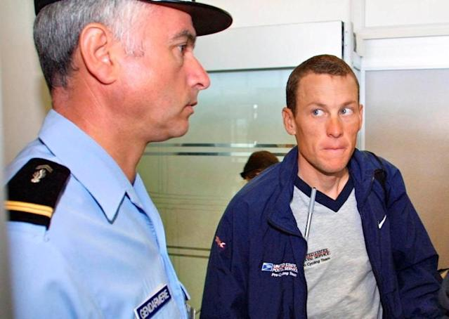 FILE PHOTO: US Postal Service team leader Lance Armstrong of the USA looking at a French gendarme before boarding for the transfer stage of the Tour de France cycling race