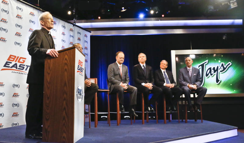 Rev. Brian Shanley, far left, Providence University President, John DeGioia, fourth from right, Georgetown University President, Randy Freer, third from right, FOX Sports President and COO, Larry Jones, second from right, and FOX Sports V.P. and Madison Square Garden Executive Vice President Joel Fisher, far right, hold a press conference on Wednesday, March 20, 2013 in New York. Big East athletic conference member schools gathered in New York to announce developments helping to shape the new basketball-focused conference. (AP Photo/Bebeto Matthews)