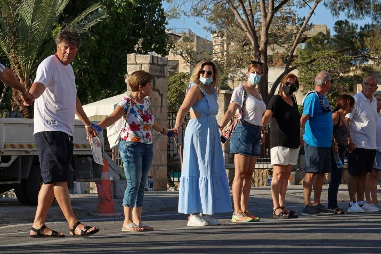 Nikos Karoullas, on the left, joins a human chain in the fenced-off area of Varosha in the self-proclaimed Turkish Republic of Northern Cyprus on July 16