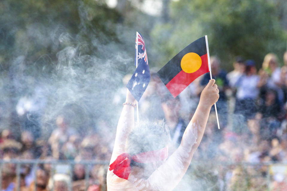 Man hold Aboriginal flag and Australian flag during Australia/ Invasion Day march