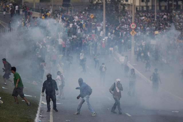 People throw tear gas back at police as they protest outside Minerao stadium where a Confederations Cup soccer match takes place between Japan and Mexico in Belo Horizonte, Brazil, Saturday, June 22, 2013. Demonstrators once again took to the streets of Brazil on Saturday, continuing a wave of protests that have shaken the nation and pushed the government to promise a crackdown on corruption and greater spending on social services. (AP Photo/Felipe Dana)