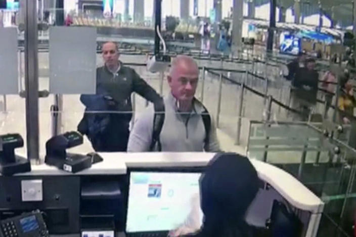 FILE—This Dec. 30, 2019 image from security camera video shows Michael L. Taylor, center, and George-Antoine Zayek at passport control at Istanbul Airport in Turkey. Taylor is accused of smuggling former Nissan Motor Co. Chairman Carlos Ghosn out of Japan in 2019 while he was awaiting trial on financial misconduct charges. (DHA via AP, File)