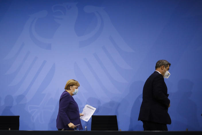 FILE - In this Wednesday, Dec. 2, 2020 file photo, German Chancellor Angela Merkel, left, and Bavarian govenor Markus Soeder, right, leave a news conference following talks of the governmnet with the federal state govenors, at the Chancellery in Berlin. The coronavirus pandemic is colliding with politics as Germany embarks on its vaccination drive and one of the most unpredictable election years in its post-World War II history. (AP Photo/Markus Schreiber, Pool, File)