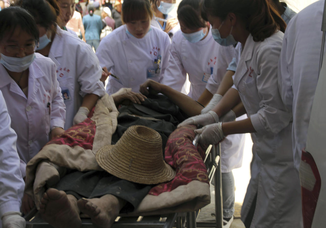 An injured resident is attended to by medical workers on the grounds of a hospital after an earthquake hit Minxian county in northwest China's Gansu province Monday July 22, 2013. A shallow earthquake struck a dry, hilly farming area in western China early Monday, killing at least 56 people, injuring more than 400, and destroying thousands of homes, the local government said. (AP Photo) CHINA OUT