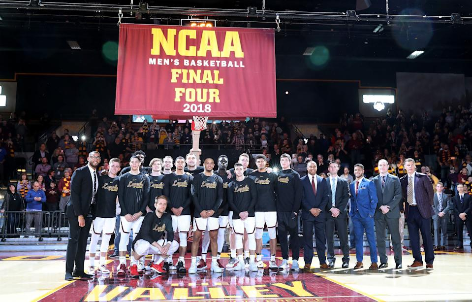 The Loyola Ramblers men's basketball team gathers for a group photograph in front of a Final Four banner during a pregame ceremony ahead of the 2018-19 season opener. (Getty)
