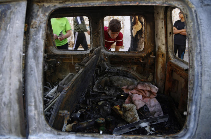 Palestinian kids look at a destroyed car after it was hit from an Israeli Airstrike near by, in Gaza City, Wednesday, May 19, 2021. (AP Photo/Hatem Moussa)