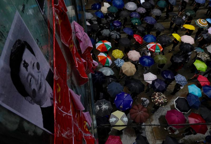Protesters carrying umbrellas march past a pedestrian bridge displaying vandalized photos of Chinese President Xi Jinping and communist party flags in Hong Kong, Sunday, Oct. 6, 2019. A group of pro-democracy Hong Kong legislators filed a legal challenge against the government's use of a colonial-era emergency law to criminalize the wearing of masks at rallies to quell anti-government demonstrations, which diminished in intensity but didn't stop. (AP Photo/Vincent Yu)