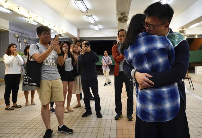 Pro-democracy candidate James Yu hugs his girlfriend after winning his seat in district council elections in Hong Kong, early Monday, Nov. 25, 2019. Vote counting was underway in Hong Kong on Sunday after a massive turnout in district council elections seen as a barometer of public support for pro-democracy protests that have rocked the semi-autonomous Chinese territory for more than five months. (AP Photo/Vincent Yu)