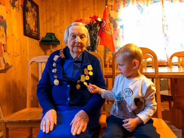 PHOTO: In this handout family photo taken by Dmitry Panov, Zinaida Korneva, World War II veteran sits during her interview with the Associated Press as her great-great grandchild Richard Panov looks at a medal in St. Petersburg, Russia, May 5, 2020. (Dmitry Panov/AP)