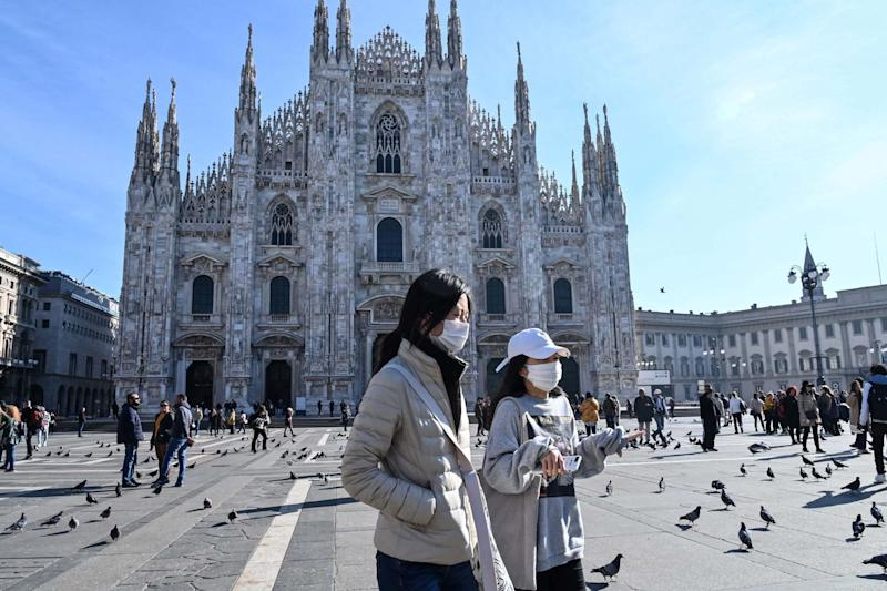 Two women wearing a protective facemask walk across the Piazza del Duomo in central Milan (AFP via Getty Images)
