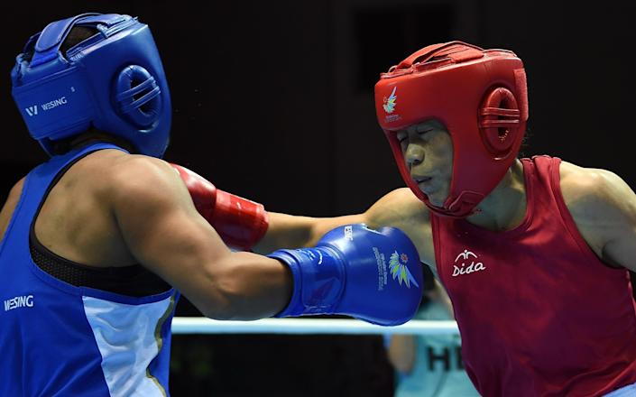 Mary Kom (right) punches Kazakhstan's Shekerbekova Zhaina during the Asian Games women's flyweight (48-51kg) boxing final in Incheon on October 1, 2014 (AFP Photo/Indranil Mukherjee)