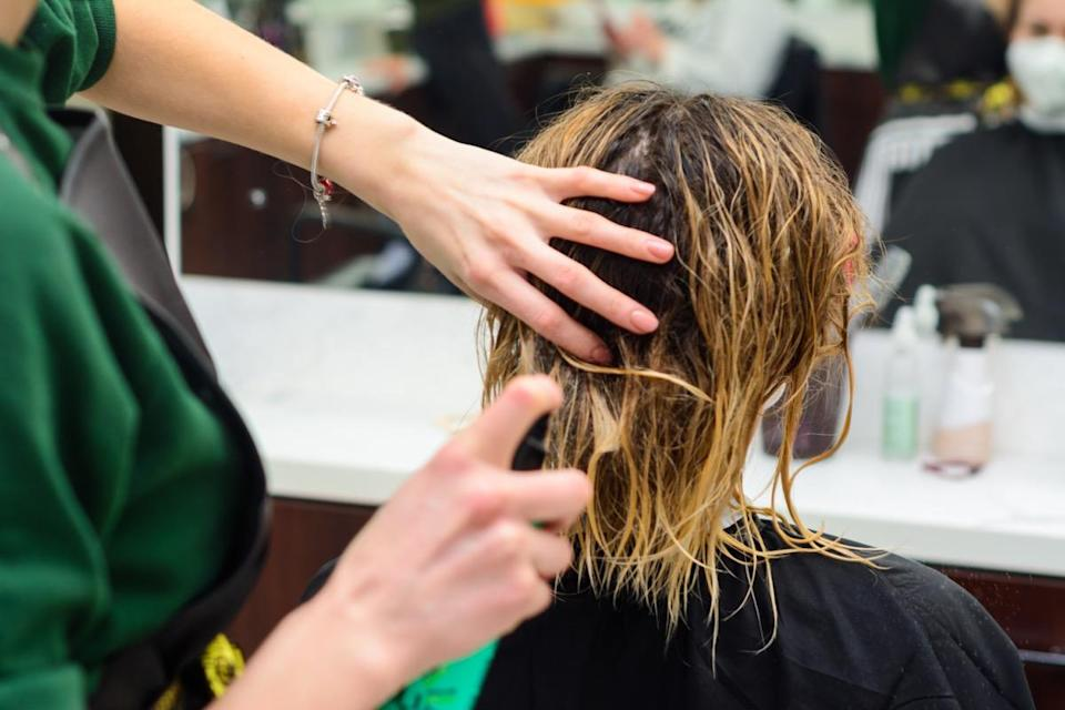 Hairdresser is cutting a woman's wet hair in the saloon.
