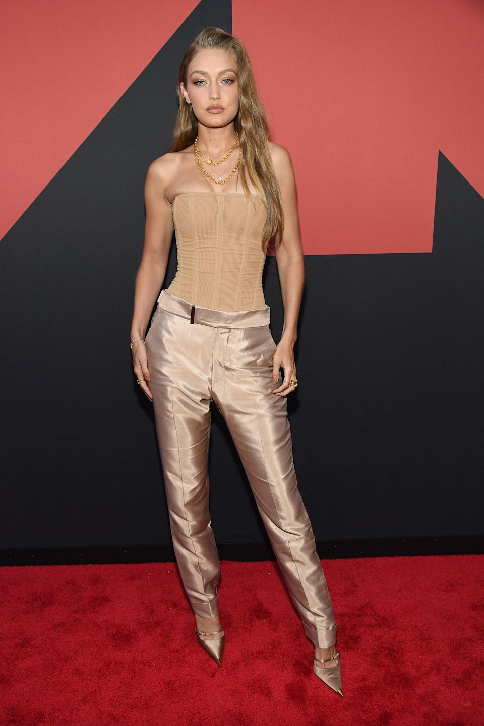 There's naked dressing, and then there's naked <em>power</em> dressing. Gigi hit the 2019 MTV Awards in a strapless skin-toned bustier bodysuit tucked into iridescent nude trousers. Her footwear matched the theme, naturally, and the chains around her neck add a touch of gold to an already luxe look.
