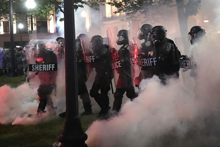 As tear gas fills the air, police try to push back demonstrators.