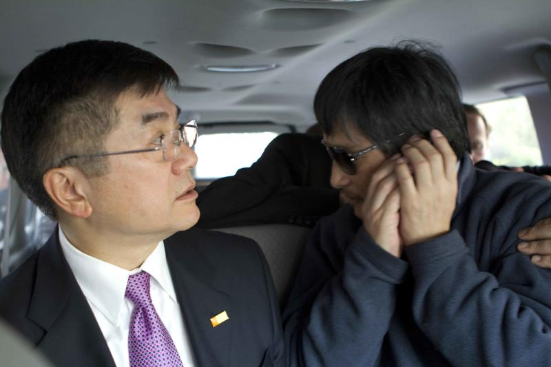 In this photo released by the US Embassy Beijing Press Office, blind lawyer Chen Guangcheng makes a phone call as he is accompanied by U.S. Ambassador to China Gary Locke in a car on the way to a hospital in Beijing Wednesday May 2, 2012. (AP Photo/US Embassy Beijing Press Office)