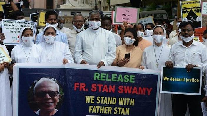 Catholic priests and nuns hold a banner during a protest against the arrest of Jesuit priest Father Stan Swamy in the eastern Indian state of Jharkhand.