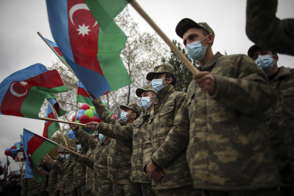Azerbaijani soldiers hold national flags as they celebrate the transfer of the Lachin region to Azerbaijan's control, as part of a peace deal that required Armenian forces to cede the Azerbaijani territories they held outside Nagorno-Karabakh, in Aghjabadi, Azerbaijan, Tuesday, Dec. 1, 2020. Azerbaijan has completed the return of territory ceded by Armenia under a Russia-brokered peace deal that ended six weeks of fierce fighting over Nagorno-Karabakh. Azerbaijani President Ilham Aliyev hailed the restoration of control over the Lachin region and other territories as a historic achievement. (AP Photo/Emrah Gurel