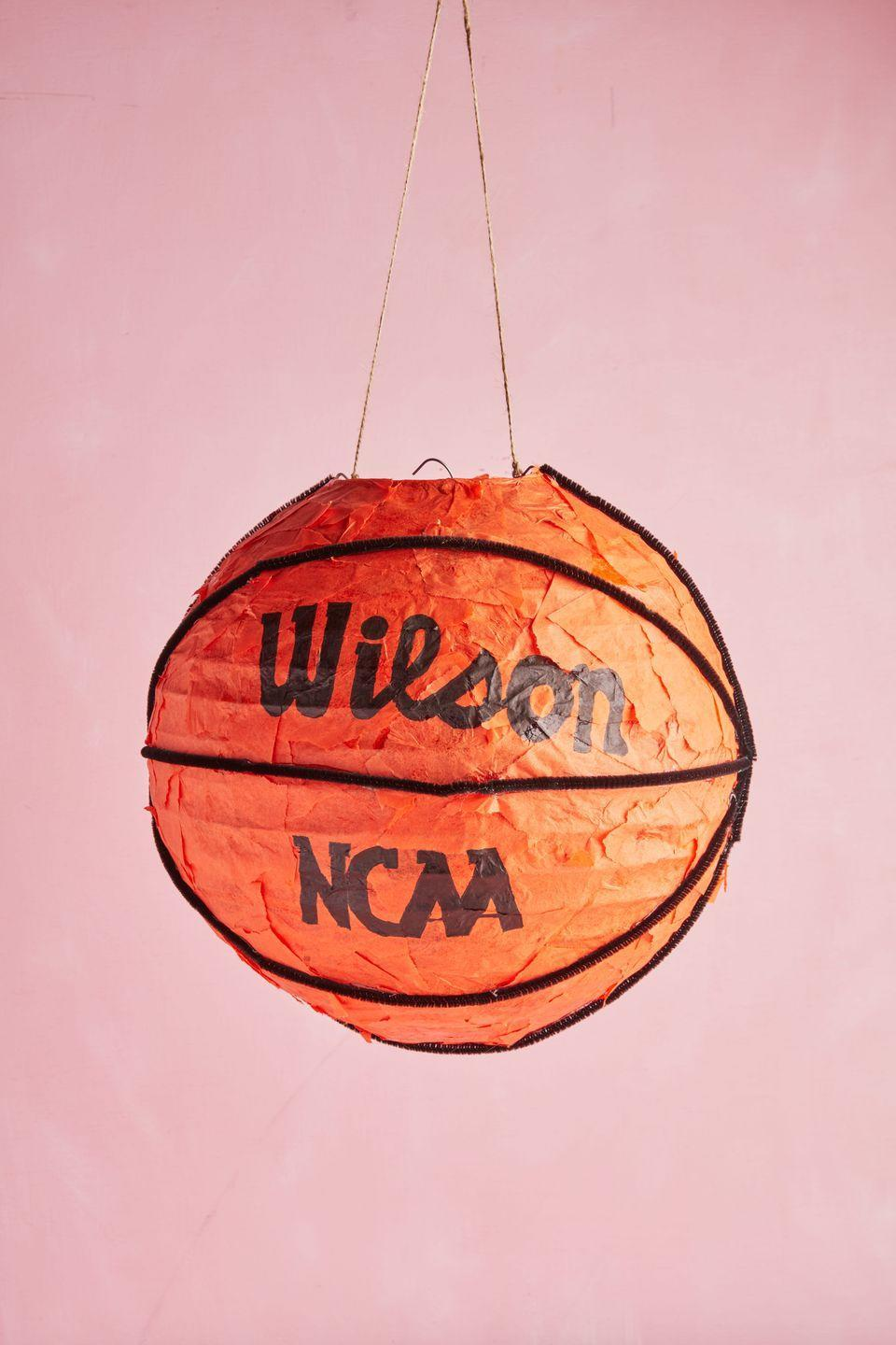 "<p>Perfect for hanging off the back of a school chair this basketball ""box"" is a real slam dunk!<strong><br></strong></p><p><strong>To make:</strong> Papier-mâché orange tissue paper to a 12-inch round paper lantern. Use black pipe cleaners to create segments, adhering with hot gun. Use a black marker to write words. Wrap twine around wire on the top of the lantern for hanging.</p><p><a class=""link rapid-noclick-resp"" href=""https://www.amazon.com/Weddingstar-Round-Paper-Lantern-White/dp/B005S4K06C/ref=sr_1_3?tag=syn-yahoo-20&ascsubtag=%5Bartid%7C10050.g.25844424%5Bsrc%7Cyahoo-us"" rel=""nofollow noopener"" target=""_blank"" data-ylk=""slk:SHOP PAPER LANTERN"">SHOP PAPER LANTERN</a></p>"