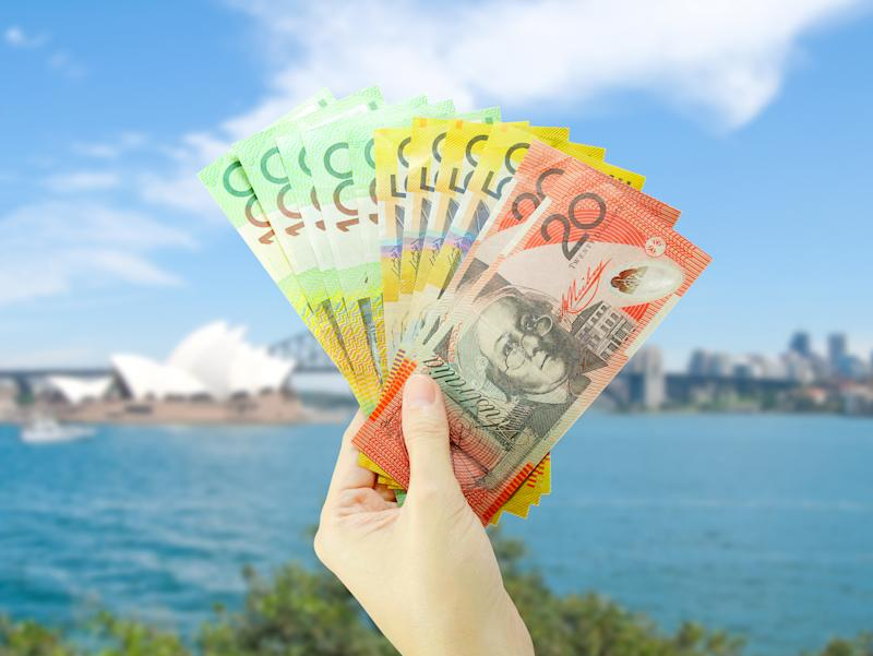 Pictured: Australian cash in hand at Sydney Harbour, suggesting wage growth in Australia. Image: Getty